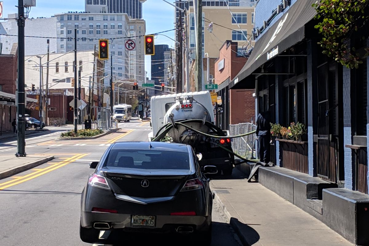 A bike lane is blocked by not one, but two automobiles.