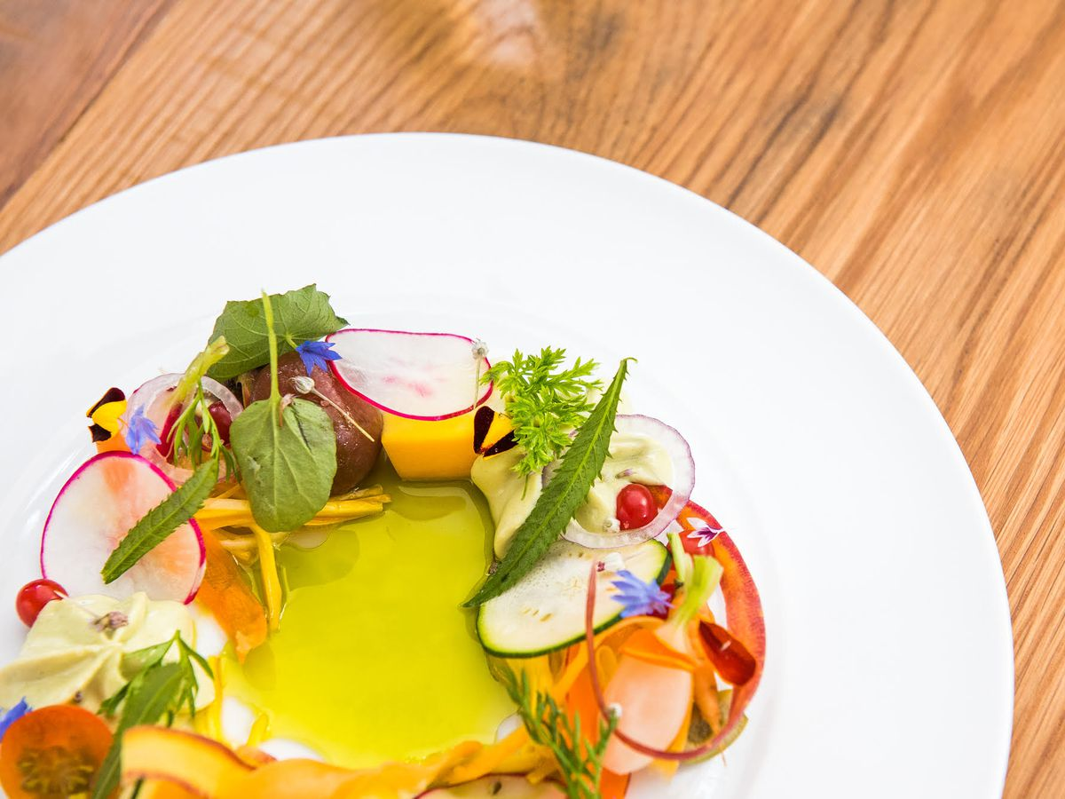 Spring vegetables from radishes to edible flowers surround a pool of lime green sauce