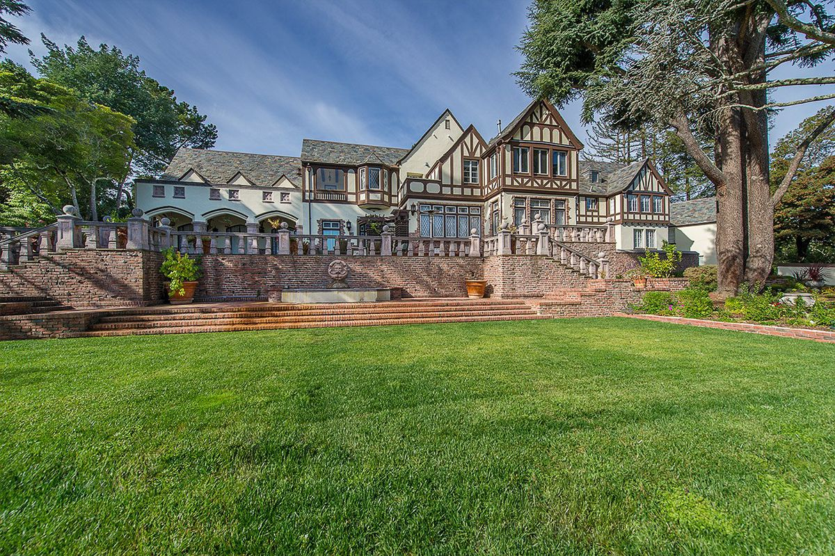 Exterior of Tudor-style mansion with a big green lawn.