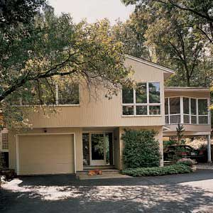 <p>Adjacent to the second-floor kitchen, the screen porch is located on top of a new carport, giving it the feel of a tree house. Note the angled bay in the middle of the porch wall.</p>