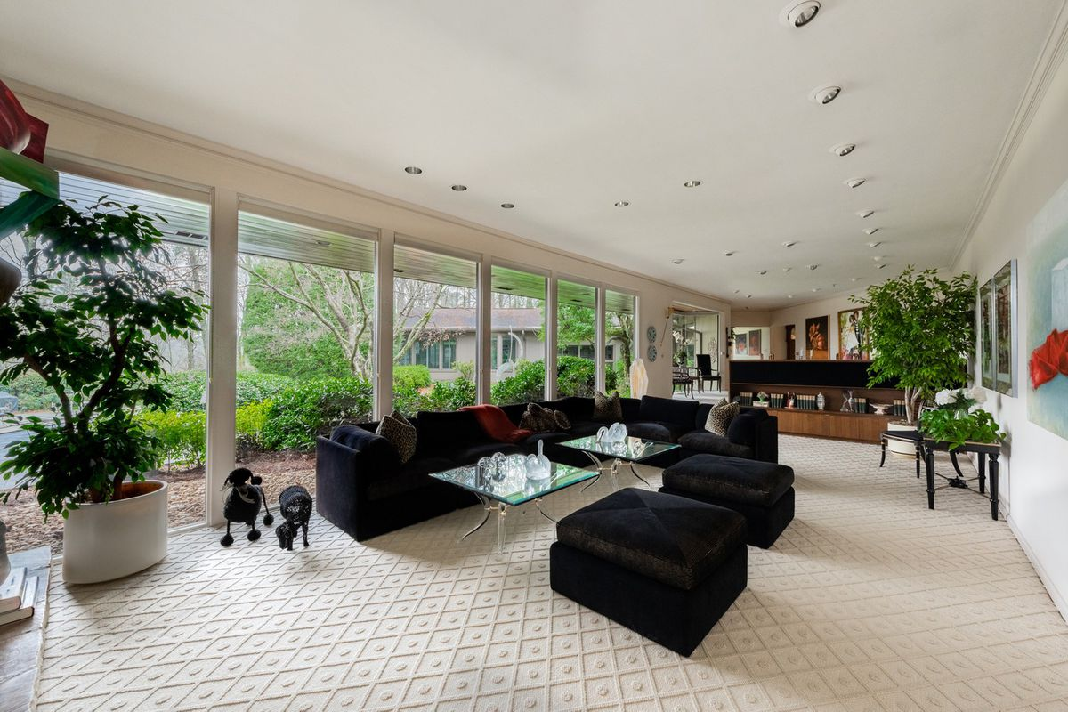 A huge living room with white carpet and white walls