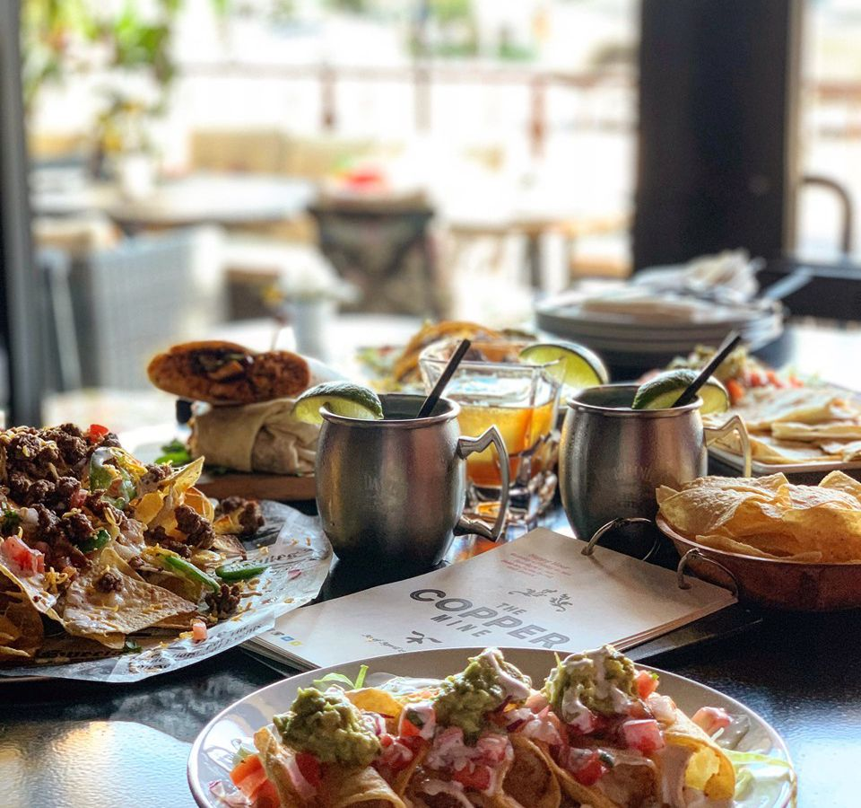 An array of dishes, including nachos, sitting at a sunny bar table.