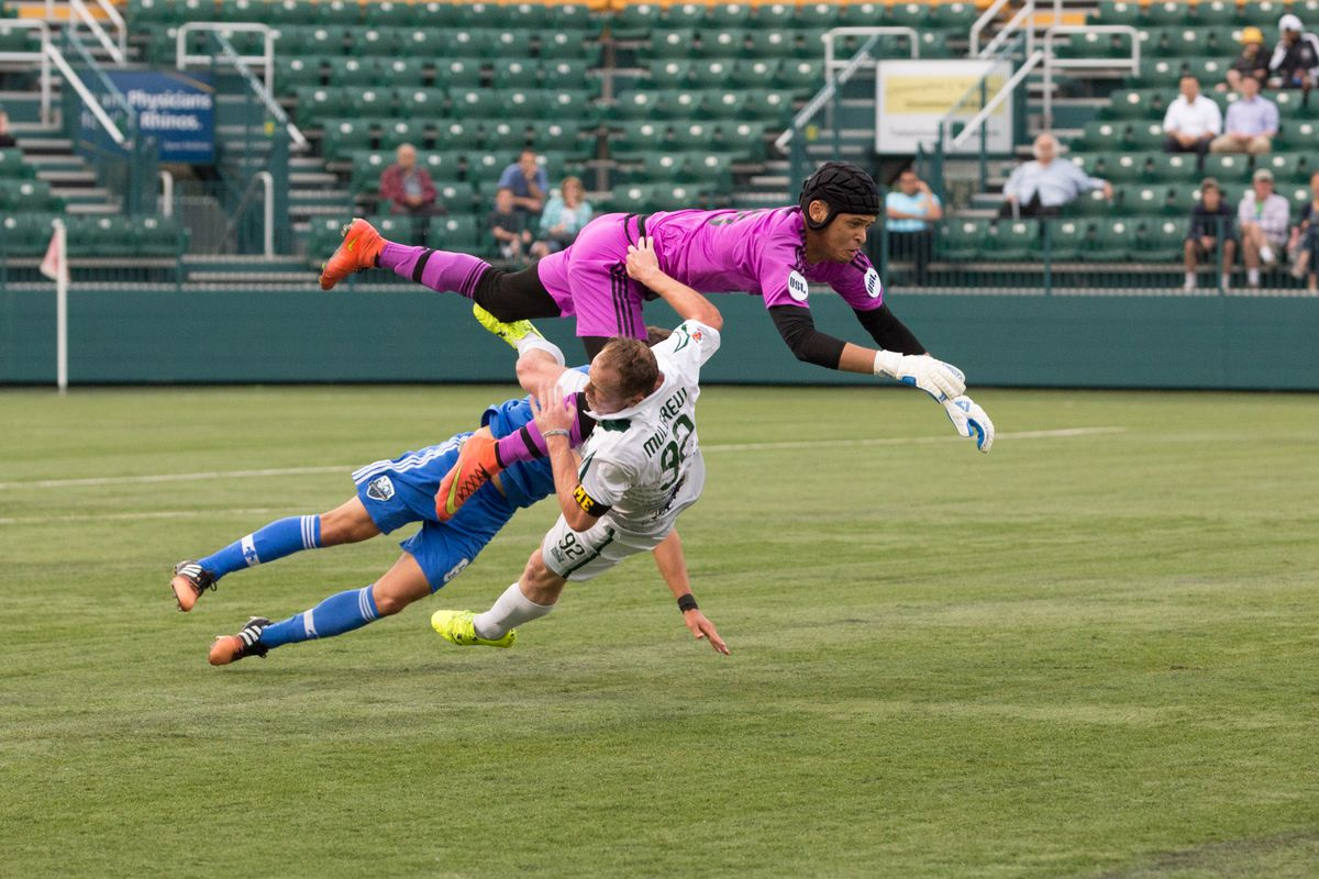 Revolution loanee Timi Mulgrew takes the full force of goalkeeper Paulmin during a collision early in the first half