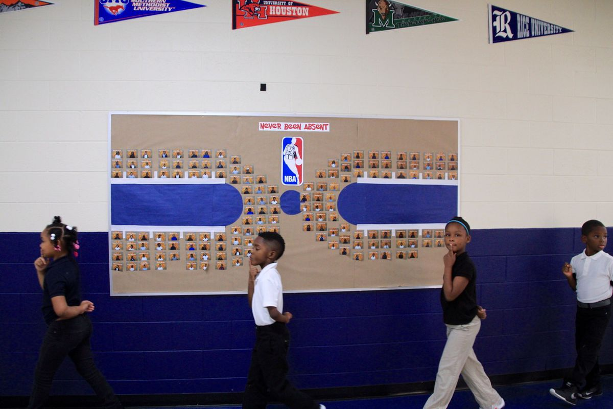 """Students walk past a """"basketball court"""" that showcases students with best attendance."""