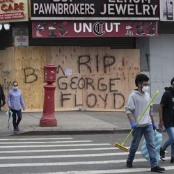 Volunteers Christian Tyler and Ashante West, right, carry brooms after participating in a community cleanup effort as they walk by a boarded up pawnbroker's store, Tuesday, June 2, 2020, in the Fordham Road area of the Bronx borough of New York. Protesters broke into stores Monday night in reaction to George Floyd's death while in police custody on May 25 in Minneapolis.