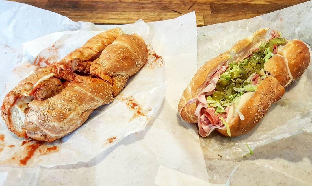 A meatball sub and an Italian sub on white deli paper