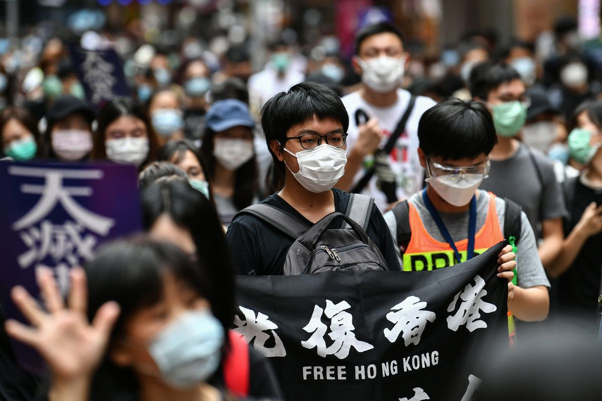 A dense crowd of protesters wearing masks holds signs; the photo focuses on a young man in glasses. He holds a black sign with with text in English and Chinese. The English text reads: Free Hong Kong.