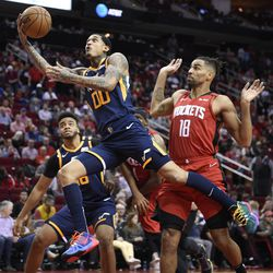 Utah Jazz guard Jordan Clarkson (00) shoots as Houston Rockets forward Thabo Sefolosha (18) defends during the second half of an NBA basketball game, Sunday, Feb. 9, 2020, in Houston.