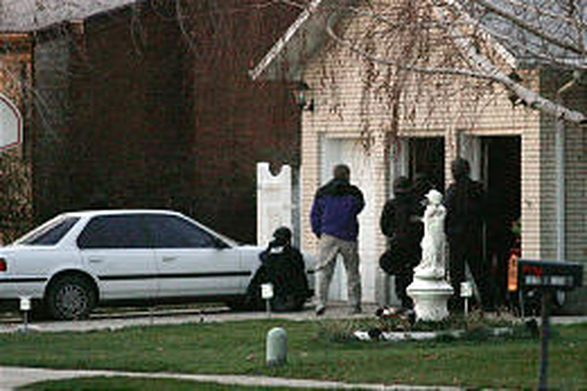 Police get into position at residence where a man is believed to have slain his brother before turning a gun on himself.