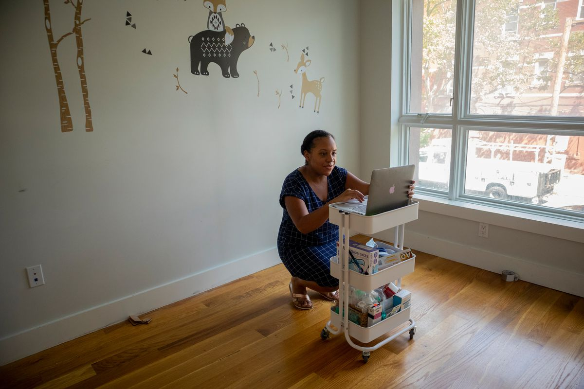 Jenny Coerbell uses one of the few unwrapped furniture pieces to prop her computer ahead of a job interview, Aug. 14, 2020.