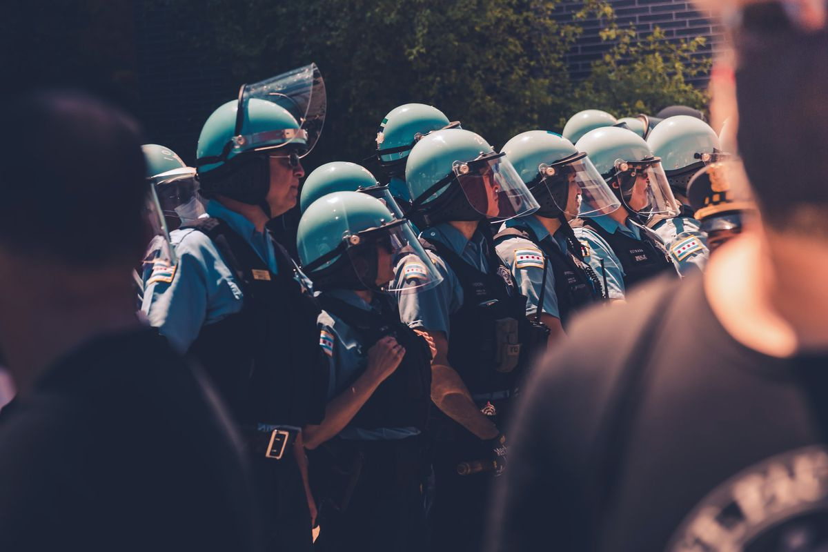 Group of police officers wearing uniforms and face shields.