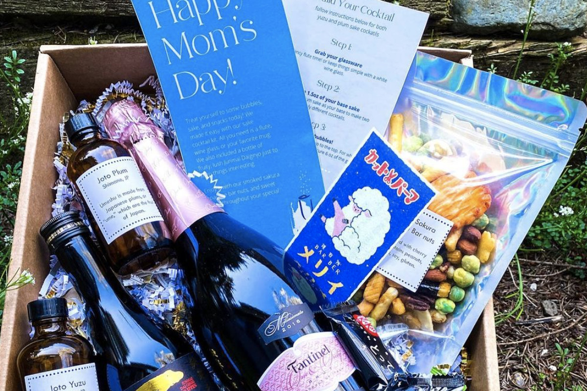 A gift box with a large bottle of rose, next to a bottle of sake, cocktail instructions, a sealed bag of colorful bar notes, and bottles of yuzu