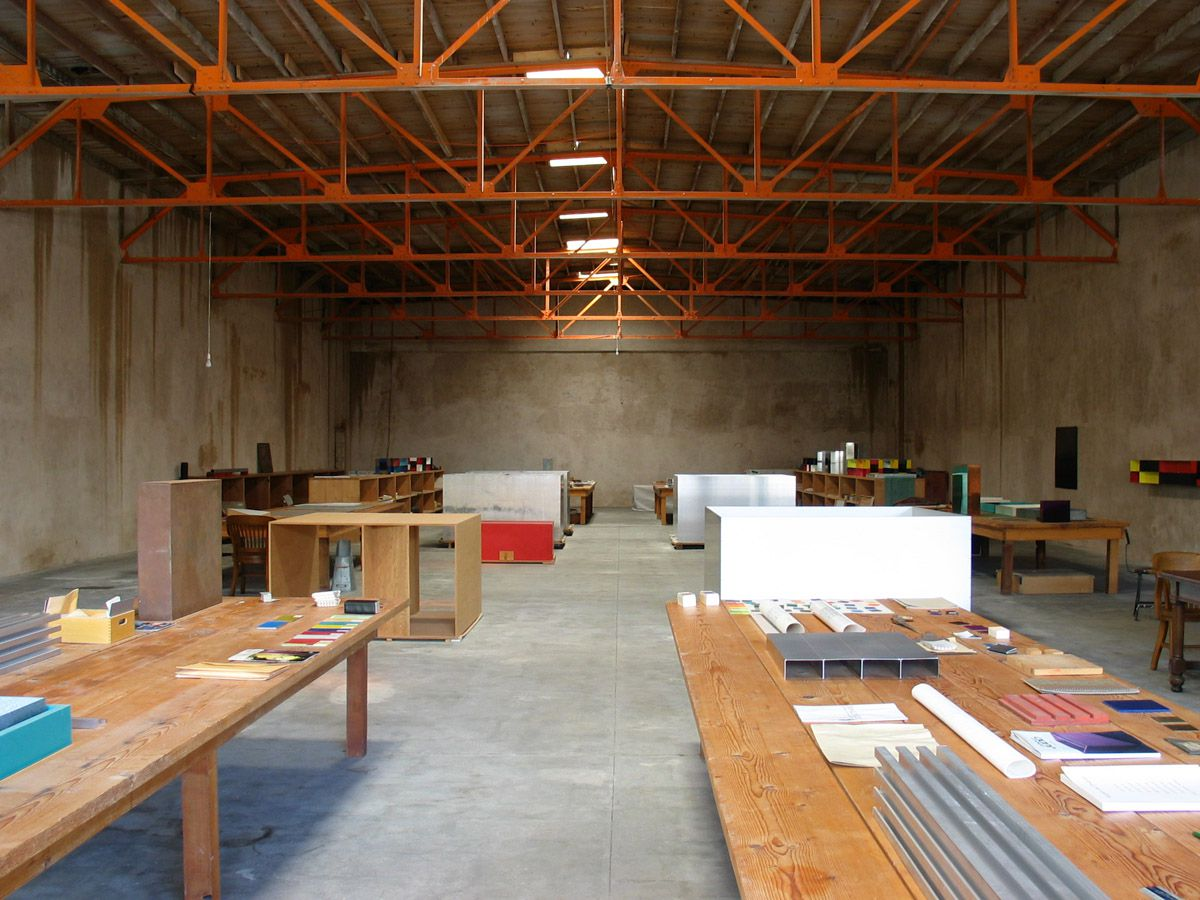 The interior of the Judd Foundation. There are wooden work tables with art supplies. The ceiling is high and has orange steel support beams.