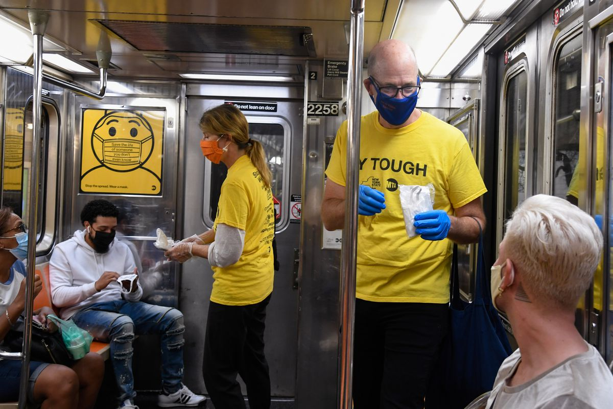 MTA Chief Transformation Officer Anthony McCord hands out PPE on a 1 train, Sept. 17, 2020.