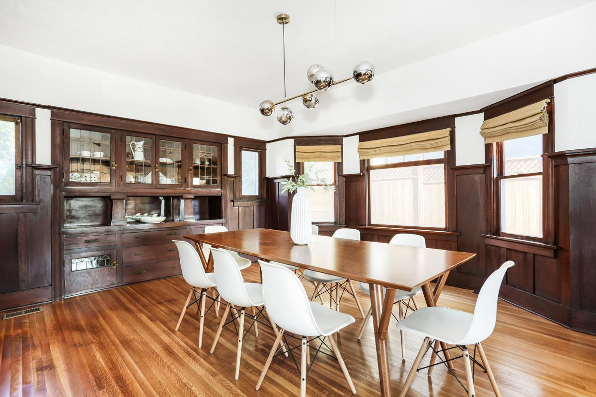 Dark-stained wood extends from almost floor to ceiling, forming a built-in hutch and wainscoting. In the center of the room, there's a rectangular wood dining table and white chairs with wood legs.