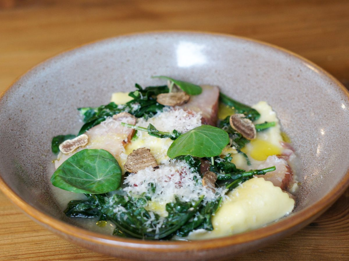 A bowl holding four ravioli, topped with greens, Parmesan cheese, and white truffle.