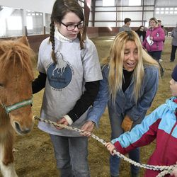 Hayley Sumner, executive director and founder of Berkshire HorseWorks, center, assists Carlie Roberts, 10, left, and Anjani Taliercio, 8, right, as they try to lead Pumpkin during an Equine Assisted Psychotherapy open house on Saturday, March 18, 2017, at Berkshire Equestrian Center in Richmond, Mass.