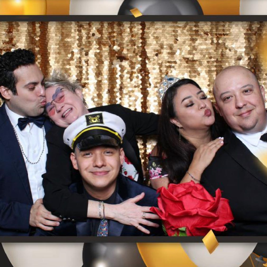 Three men and two women posing against a glittery gold backdrop in a photo booth