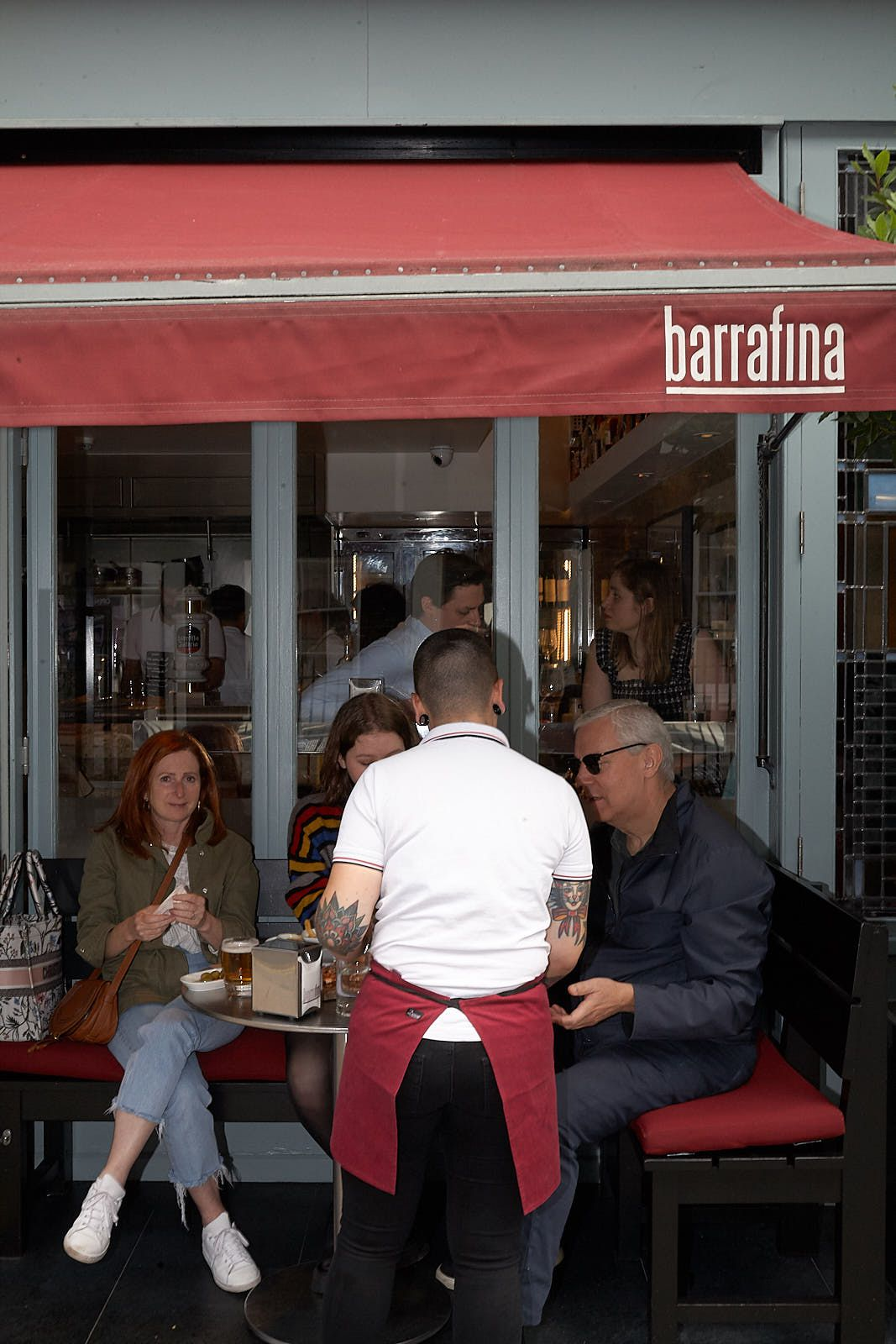 A waiter attends a table outside Barrafina in Soho