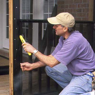 Man Installs Screen In Lower Portion Of Walls And Doors of Porch Screen