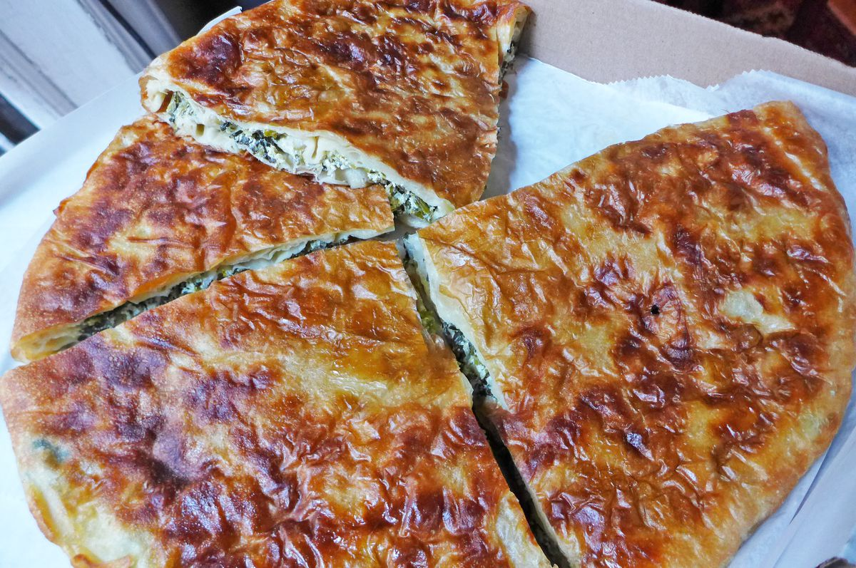 Spinach and cheese flaky phyllo pie spread out so you can see the filling.