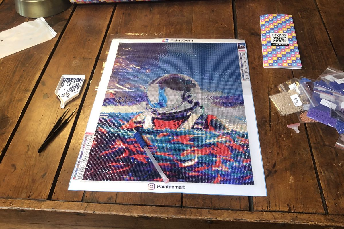 A gem painting canvas featuring an astronaut wading in the ocean