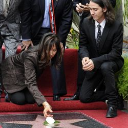 Former Beatle George Harrison's widow Olivia lays a white flower down on his new star as Harrison's son Dhani looks on during a posthumous Hollywood Walk of Fame star dedication for the late Beatle in Los Angeles, Tuesday, April 14, 2009. (AP Photo/Chris Pizzello)