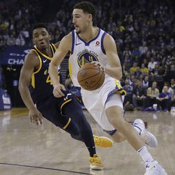 Golden State Warriors guard Klay Thompson (11) drives against Utah Jazz guard Donovan Mitchell (45) during the first half of an NBA basketball game in Oakland, Calif., Wednesday, Dec. 27, 2017. (AP Photo/Jeff Chiu)
