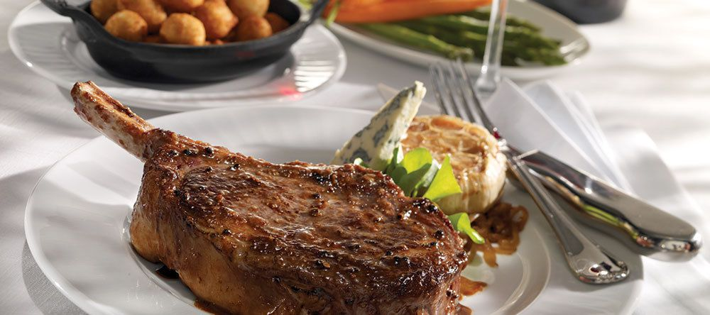 A thick steak on the bone sits on a white plate. There's a white tablecloth on the table, and side dishes are visible.