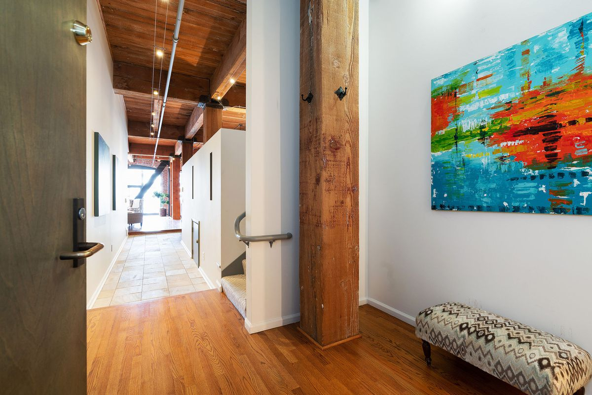 An entry hallway has wood floors, a small bench, and an abstract colorful painting.