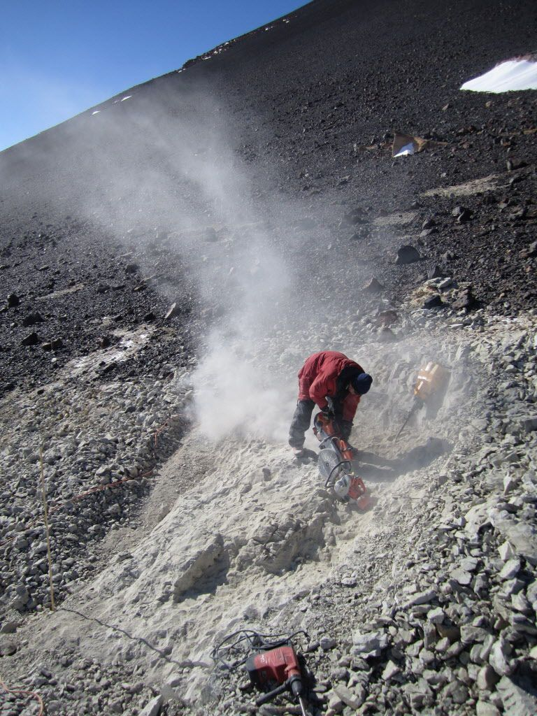 The Field Museum's chief dinosaur scientist, Peter Makovicky, cuts through rock at 13,000 feet on Mount Kirkpatrick in Antarctica in 2010.
