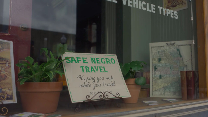 "A sign on display in a shop window reads, ""Safe Negro Travel. Keeping you safe while you travel. Inquire within."""