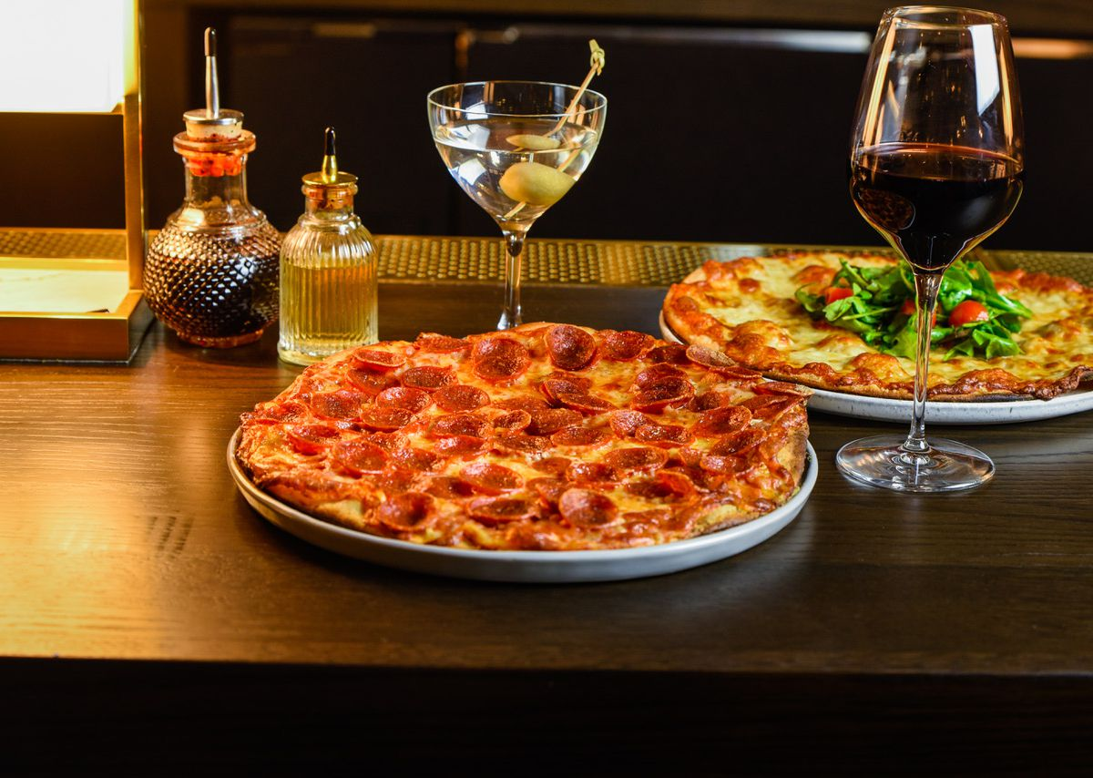 A round pepperoni pizza flanked by two glasses of wine.