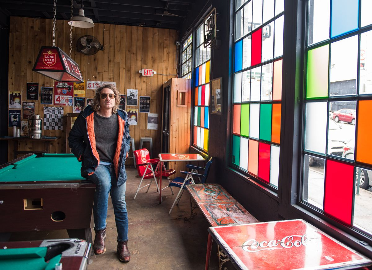 The manager at Barracuda leaning on the pool table at the venue, next to a large window with some stained glass colored panels.