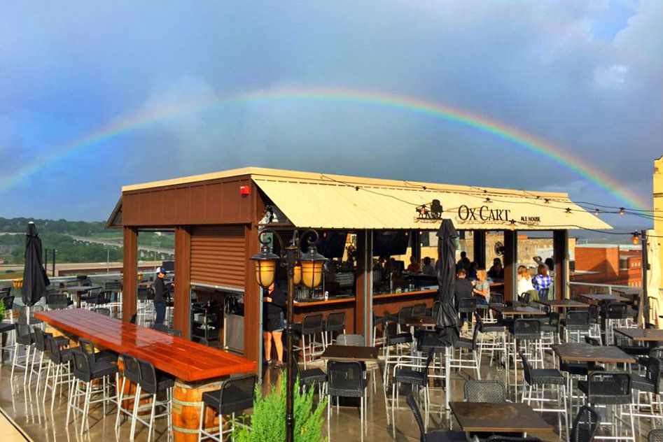 Open rooftop bar with a yellow awning and outdoor seats are all under a rainbow just after a storm