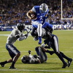 Taysom Hill (4) of the Brigham Young University Cougars hurdles Daniel Gray (1) of the Utah State Aggies as he goes in for a touchdown during NCAA football in Provo, Friday, Oct. 3, 2014.