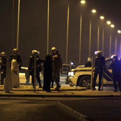 """Riot police keep villagers back from the site where a Bahraini youth was killed during an anti-government protest, allegedly by police shotgun fire, in the western village of Sadad, Bahrain, early Saturday, Sept. 29, 2012. An Interior Ministry statement said a police patrol was attacked with petrol bombs and iron rods, and one person died when """"policemen defended themselves."""" A witness among protesters said demonstrators were marching against the government when a policeman suddenly stepped out near the youth and shot him at close range."""