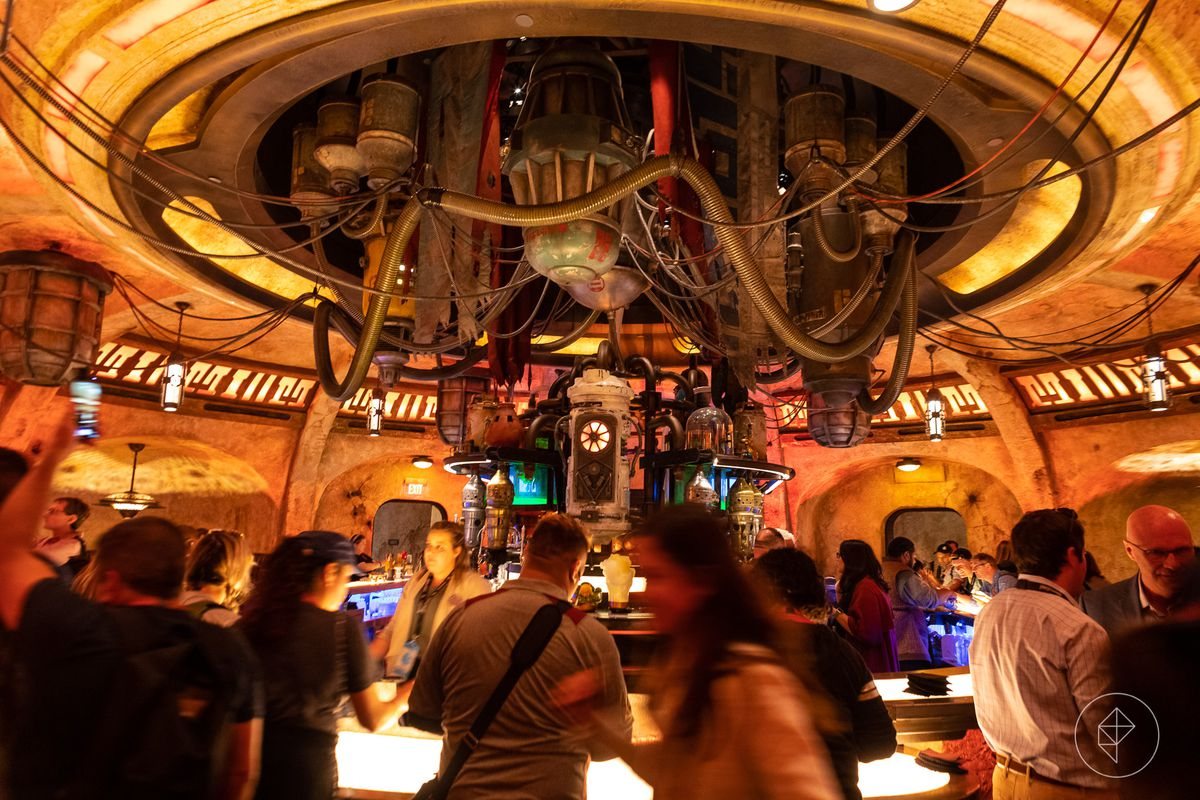 The interior of a building at Galaxy's Edge in Disneyland. The ceiling has an intricate web of pipes and structures hanging from a circular space.