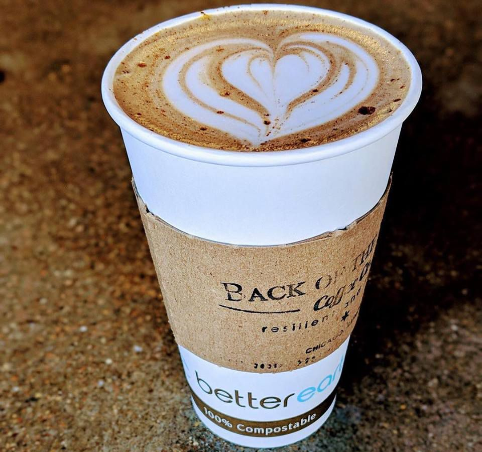 A tall white coffee cup holds an espresso drink with heart-shaped latte art.