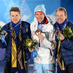 Teodor Peterson (SWE), left, Ola Vigen Hattestad (NOR), middle, and Emil Joensson (SWE) pose with their medals during the medal ceremony for the mens' cross country sprint free