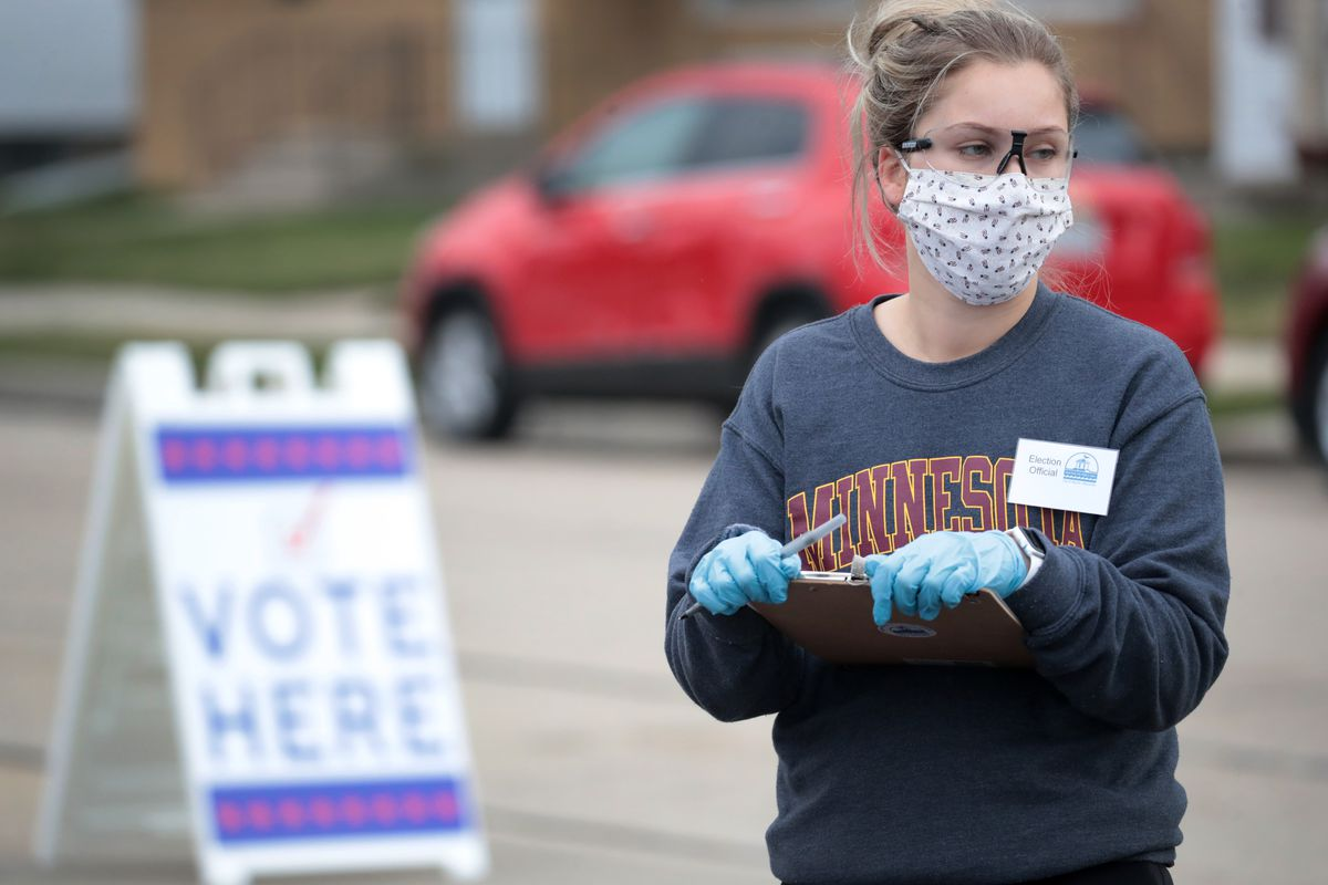 """A woman holding a clipboard and wearing a mask next to a """"vote here"""" sign."""