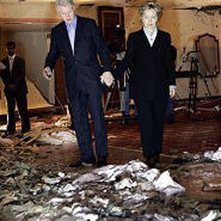 Former President Bill Clinton and his wife, Sen. Hillary Clinton, inspect bomb damage to the Radisson SAS Hotel in Amman, Jordan, Sunday.