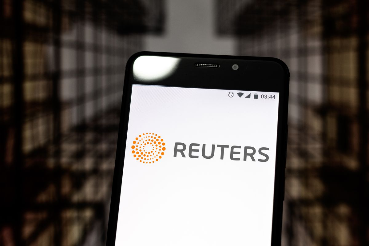 In this photo illustration a Reuters logo seen displayed on...