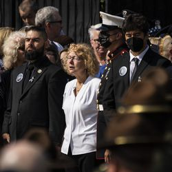 Chicago Police Officer Ella French's mother, Elizabeth French (in white) and brother Andrew French (left, with beard), stand with other family members and watch as pallbearers carry her casket into St. Rita of Cascia Shrine Chapel for Officer French's funeral, Thursday morning, Aug. 19, 2021. Officer French was fatally shot and her partner was critically wounded while in the line of duty on Aug. 7 in West Englewood.