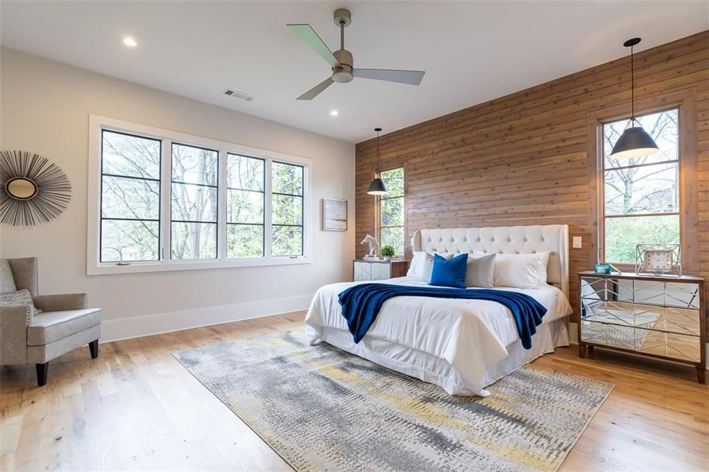 A big white master bedroom with a wooden wall at right.