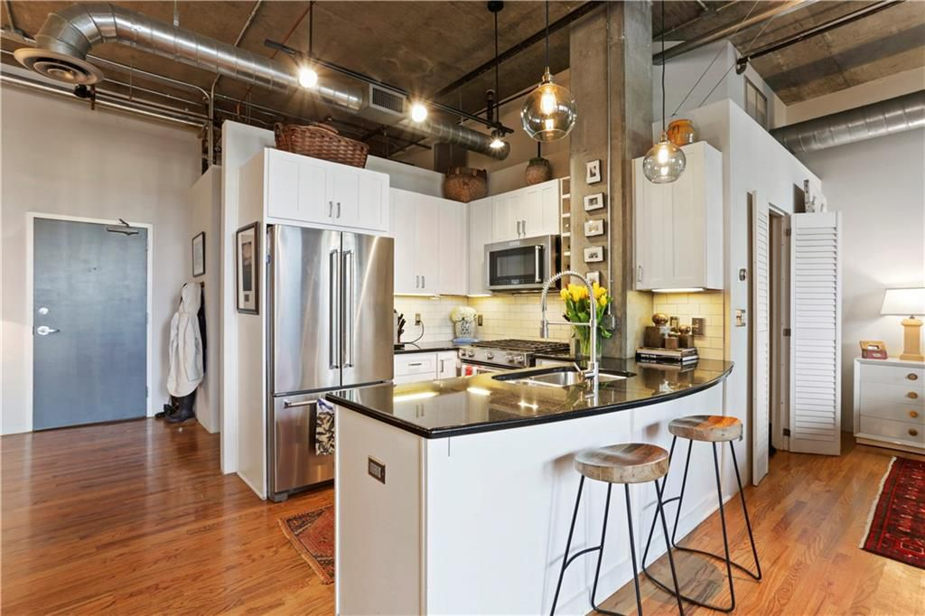 A huge loft with white kitchen and concrete walls and high ceilings.