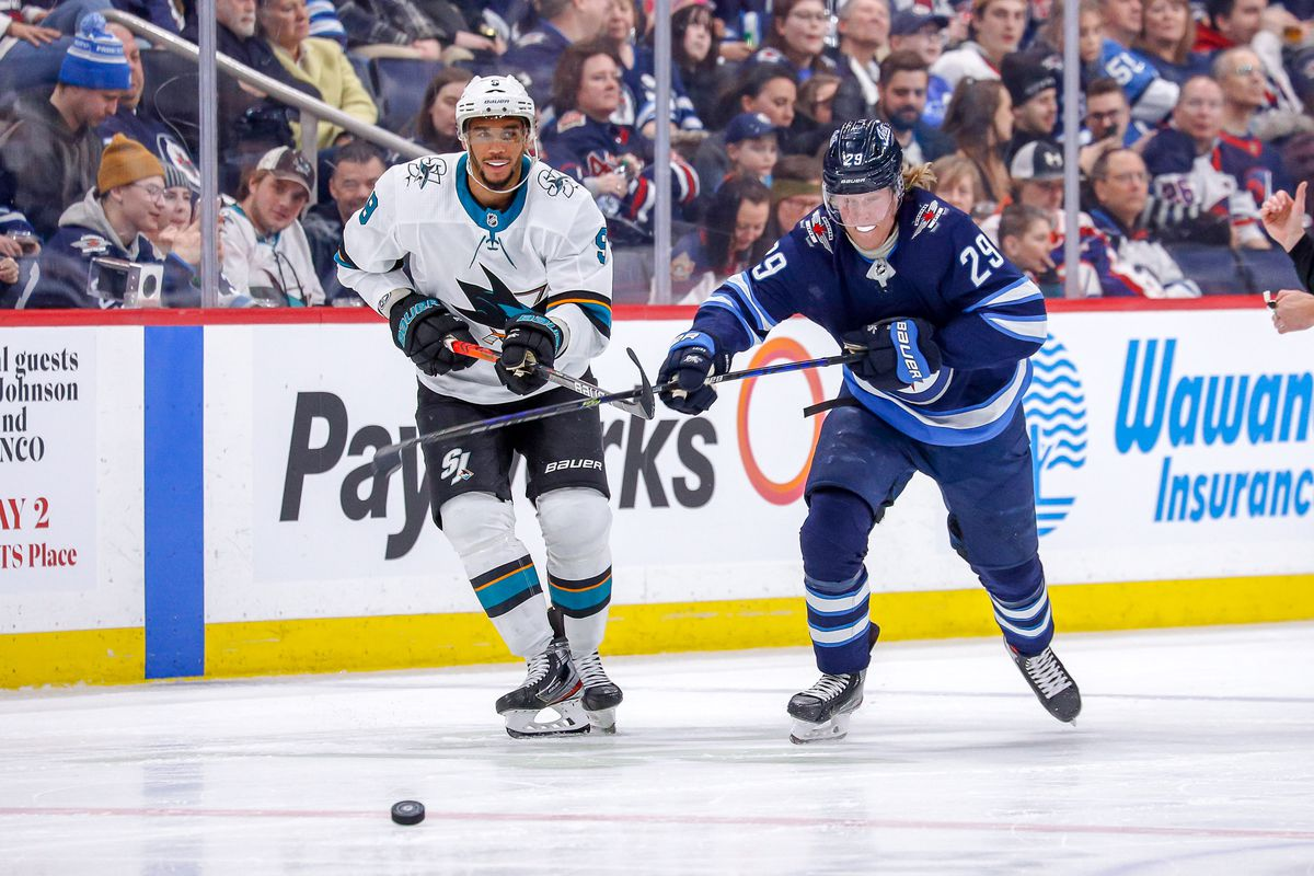 WINNIPEG, MB - FEBRUARY 14: Evander Kane #9 of the San Jose Sharks and Patrik Laine #29 of the Winnipeg Jets chase the puck down the ice during second period action at the Bell MTS Place on February 14, 2020 in Winnipeg, Manitoba, Canada.