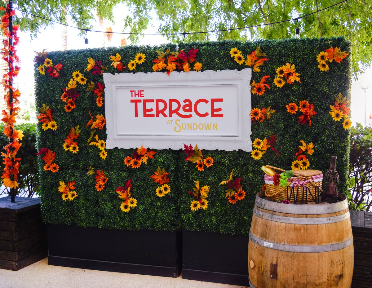 """A wall of ivy with orange and yellow flowers and a sign that says, """"The Terrace at Sundown."""""""