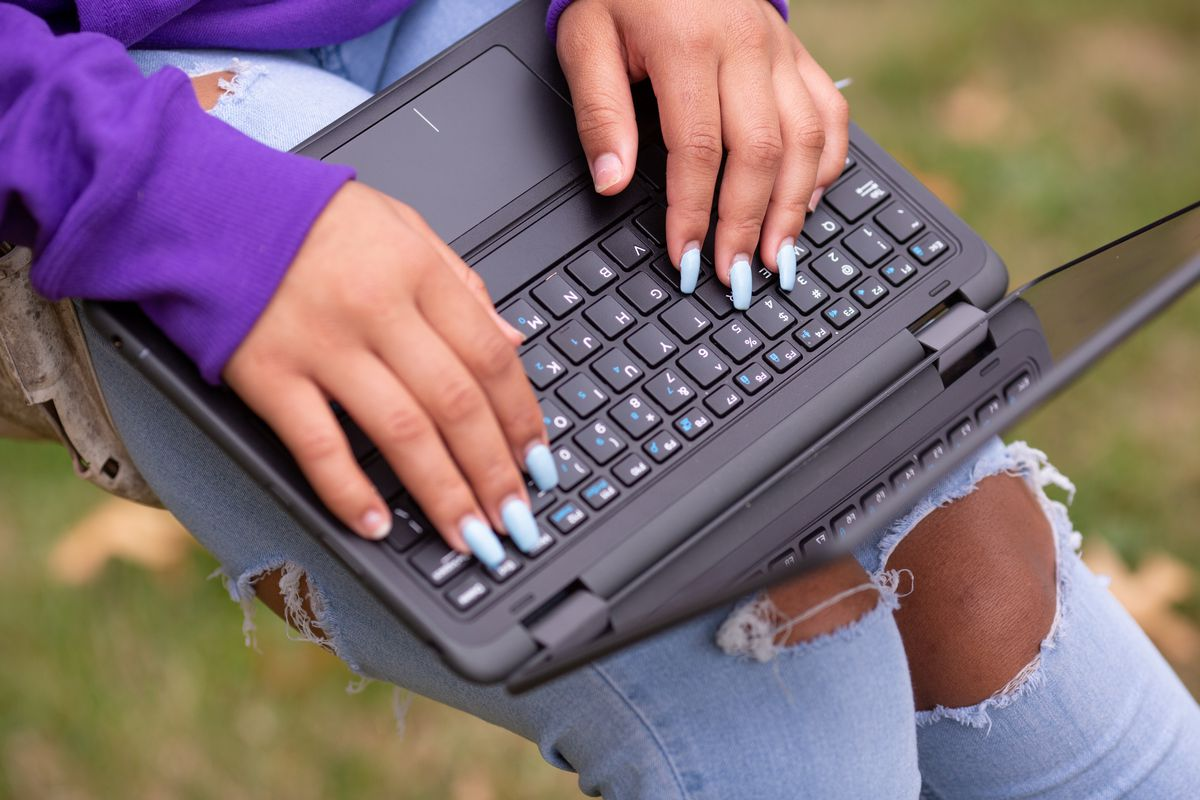 Close-up of a student's hands typing on a laptop.