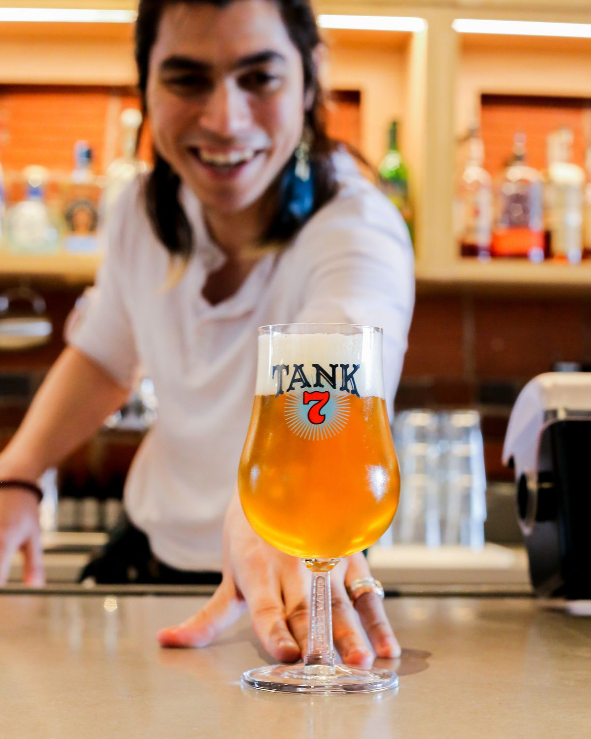 A male bartender slides forward a Tank 7 beer tulip towards the camera.